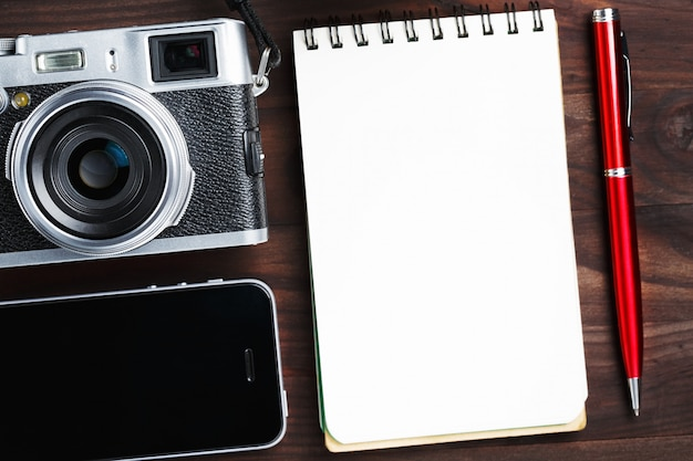Classic camera with blank notepad page and red pen on dark brown wooden table, vintage table with telephone and green flower