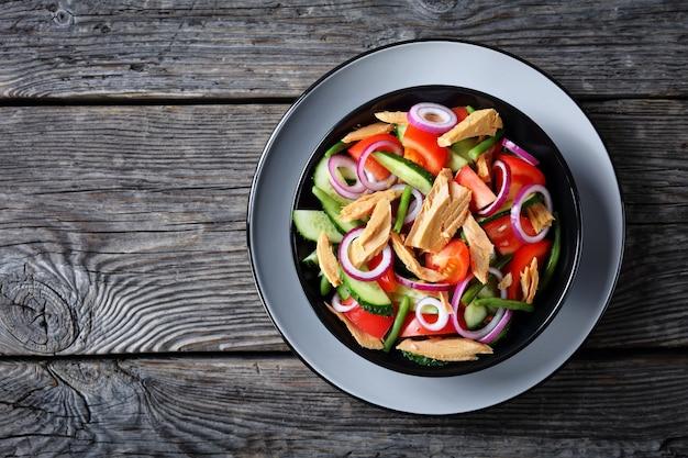 Классический консервированный салат из тунца с зеленой фасолью, огурцом с помидорами и кольцами красного лука на черной тарелке на старом деревянном фоне
