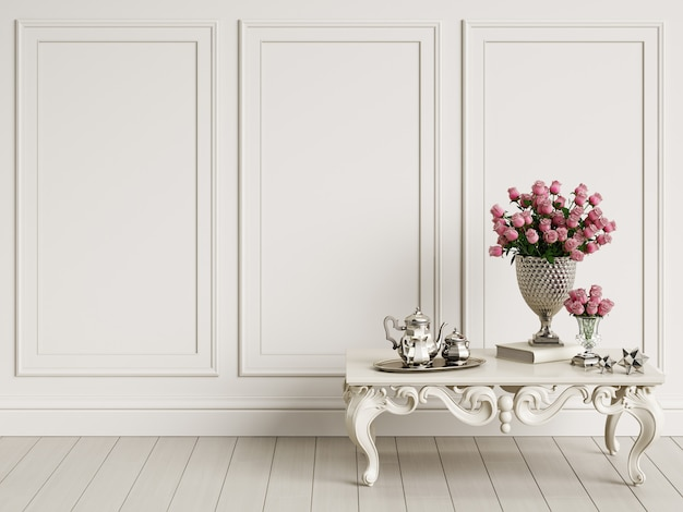 Classic carved table with bouquet of roses and silver coffee set in classic interior with copy space