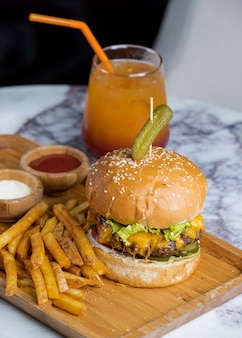 Classic cheeseburger with french fries and multivitamin juice