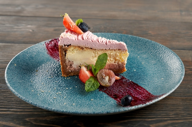 Cheesecake classica con frutti di bosco su piatto decorato