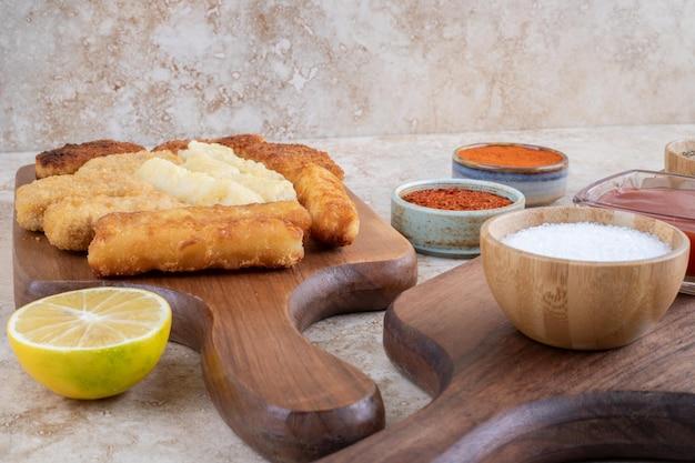 Bocconcini di pollo classici, salsiccia e bastoncini di formaggio su un piatto di legno.