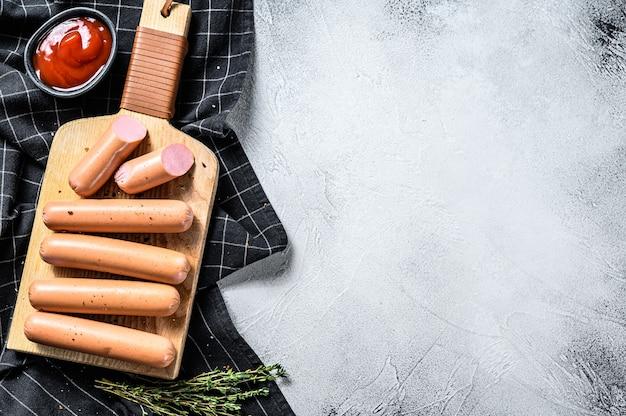 Классические куриные сосиски на разделочной доске с розмарином и специями. черный фон