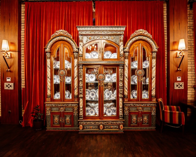 Classic china cabinet in front of the red long curtains at restaurant hall
