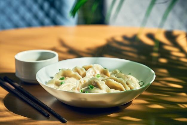 Классические китайские вареные пельмени с мясом и острым соевым соусом в белой тарелке. китайская кухня Premium Фотографии