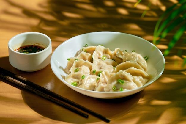 Классические китайские вареные пельмени с мясом и острым соевым соусом в белой тарелке. китайская кухня