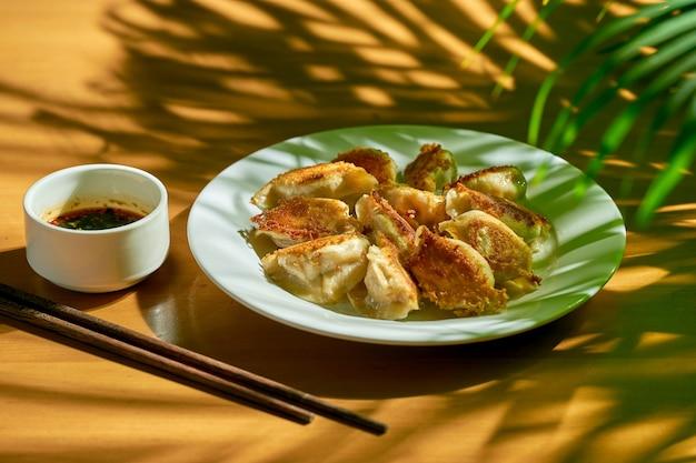 Классические китайские жареные пельмени с мясом и острым соевым соусом в белой тарелке. китайская кухня