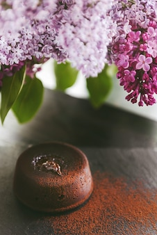 Classic chocolate fondant on a dark background with flowers