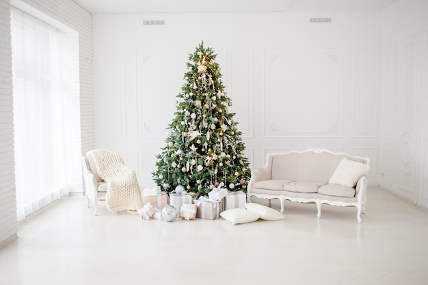 Classic christmas new year decorated interior room new year tree. christmas tree with gold decorations. modern white classical style interior design