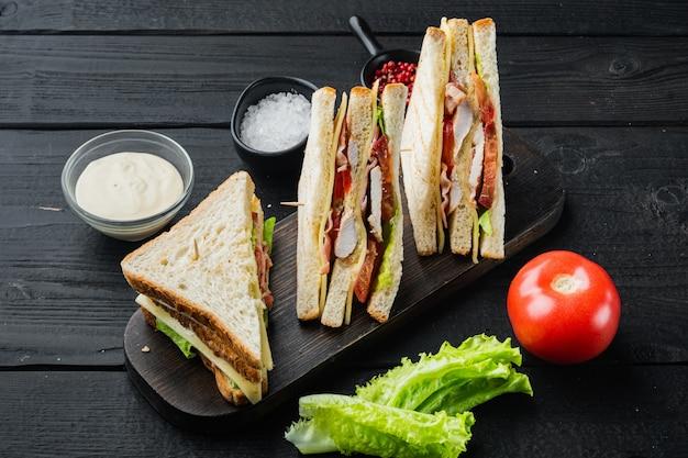 黒い木製のテーブルの上に、肉と古典的なクラブサンドイッチ