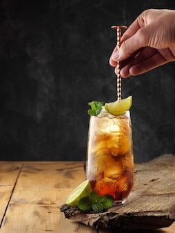 Classic cocktail cuba libre on a wooden table, copy space.