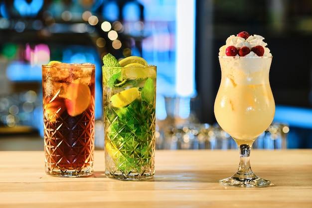 Classic cold cocktails - rum and cola, mojito and pina colada