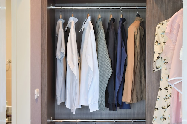 Classic color shirts are hanging in open wooden wardrobe