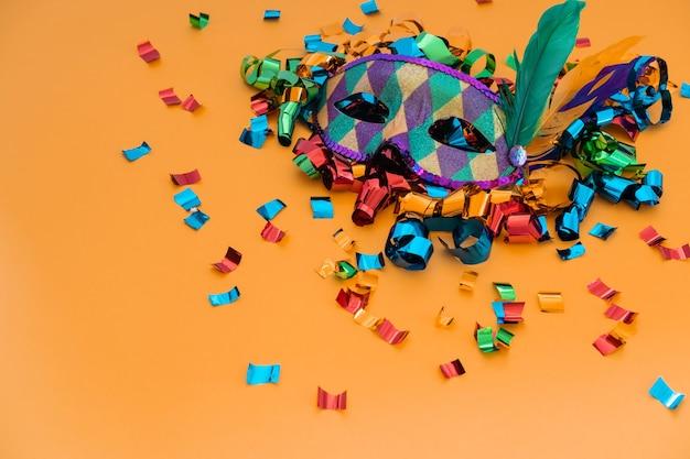 Классическая красочная карнавальная маска с перьями и конфетти на цветном фоне.