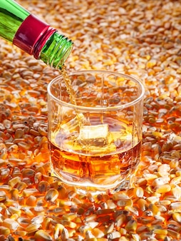 Классический кукурузный виски (бурбон) наливается в бокал, который стоит на светящихся кукурузных семенах. вертикальное фото, копировать пространство.
