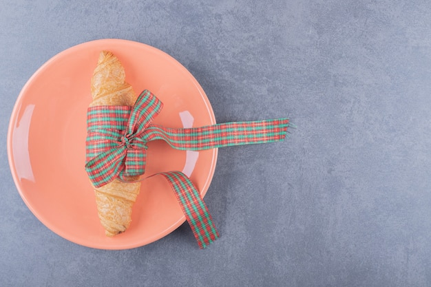 Classic croissant on orange plate over grey background. Free Photo