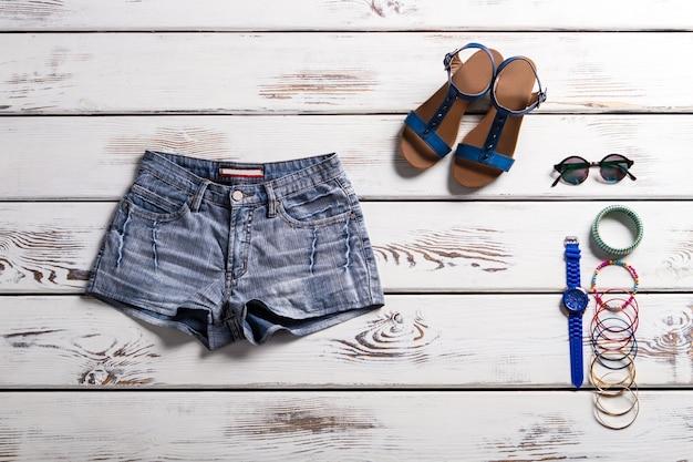 클래식 데님 반바지와 신발. 여름 의류 쇼케이스. 빈티지 반바지와 멋진 액세서리. 샌들, 반바지 및 작은 액세서리.