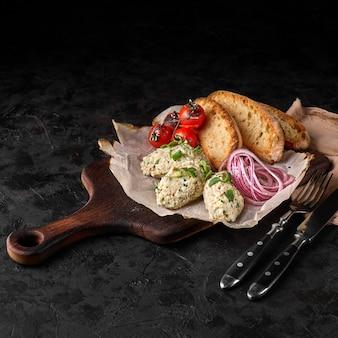 Классическое блюдо израильской кухни - сельдевый форшмак с гренками, поданный в белой тарелке на мраморном фоне. морепродукты.
