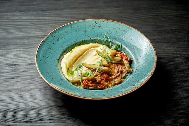 Классическое блюдо русской кухни бефстроганов с картофельным пюре в синей тарелке на деревянном фоне