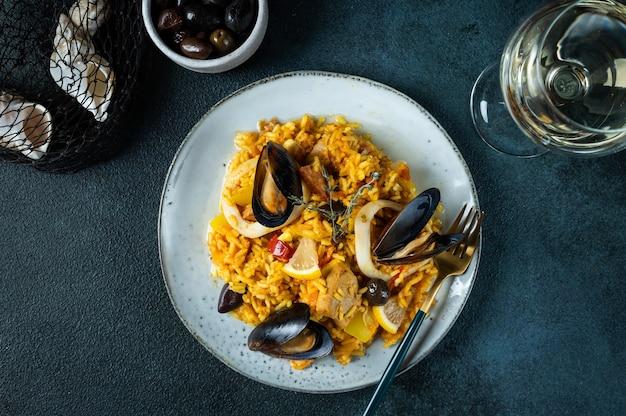 스페인의 고전적인 요리, 파란색 배경 위에 있는 접시에 해산물 빠에야. 새우, 클램프, 홍합, 신선한 레몬을 곁들인 스페인 빠에야. 스페인 음식. 컴포트 푸드. 해산물을 곁들인 밥.