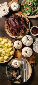 リンゴと付け合わせを添えたクラシックな料理のローストした艶をかけられたアヒル