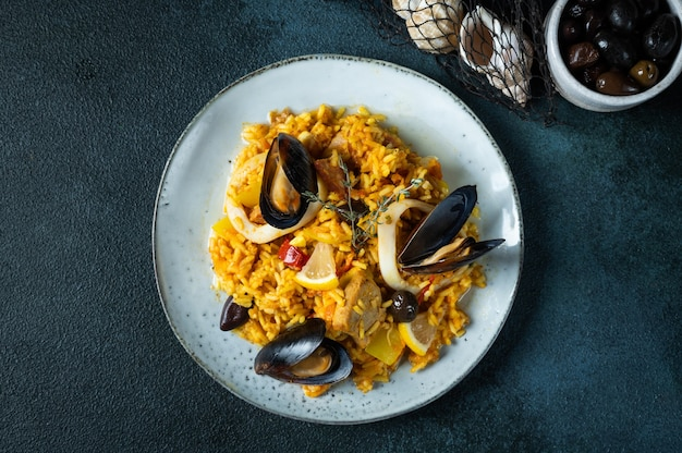 Classic dish of spain, seafood paella in plate on blue background top view. spanish paella with shrimps, clamps, mussels and fresh lemon. spanish food. comfort food. rice with seafood.