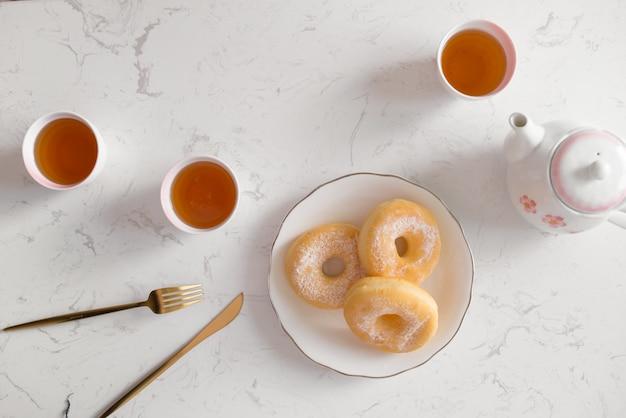 クラシックドーナツ。自宅のリビングルームのテーブルでお茶と朝の朝食。