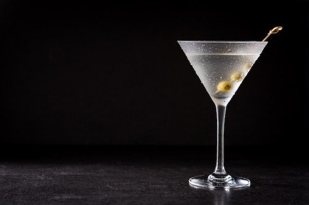 Classic dry cocktail with olives on black background copy space