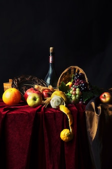 Classic dutch still life with dusty bottle of wine and fruit on a dark, vertical.