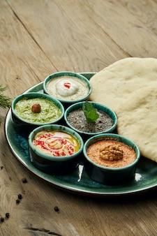 Классические восточные закуски с пита - мезе. набор в небольшой миске - хумус, паста из острого перца, часто с грецкими орехами, йогурт, паста из баклажанов.