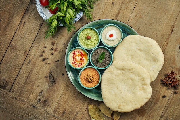 Classic eastern snacks with pita - meze. set in small bowl - hummus, hot pepper paste often with walnuts, yogurt, eggplant paste.