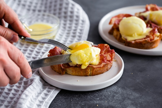 Classic eggs benedict with bacon, hollandaise sauce, english breakfast with tasty toasts