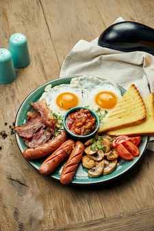 Classic english breakfast: toasts, smoked sausages, bacon, fried eggs, beans and fried toasts on a blue plate. top view, horizontal. wooden surface