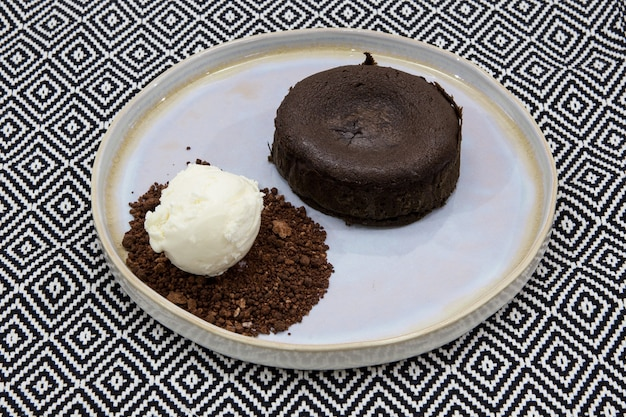 Classic fondant with liquid chocolate center. served with homemade ice cream and chocolate ground. close-up.