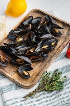 흰색 배경에 있는 나무 쟁반에 있는 고전적인 프랑스 식사 moules mariniere marinara 세트