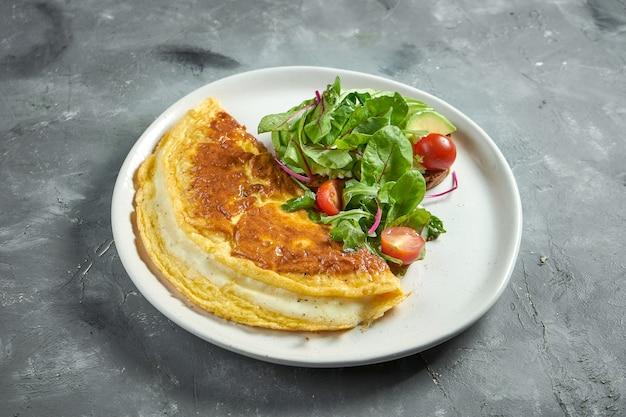 녹은 치즈와 샐러드를 곁들인 클래식 프렌치 오믈렛과 체리 토마토, 아보카도가 회색 표면에 흰색 접시에 담겨 있습니다.