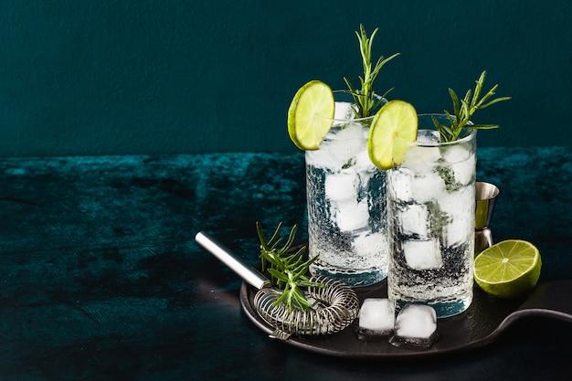 Классический джин-тонический коктейль с веточками розмарина в высоких бокалах на столе с барными аксессуарами