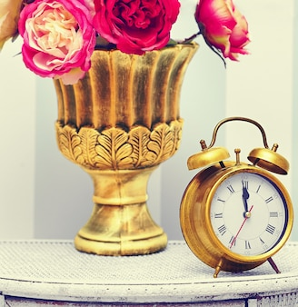 Classic gold clock  watch in bright colorful retro interior behind red flowers