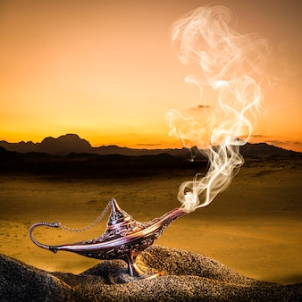 Classic gold-colored aladdin lamp laid on the sand of a dune with smoke coming out.