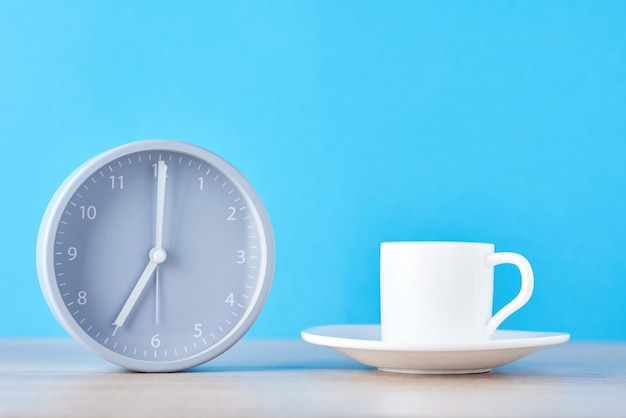 Classic gray alarm clock and white coffee cup on a blue