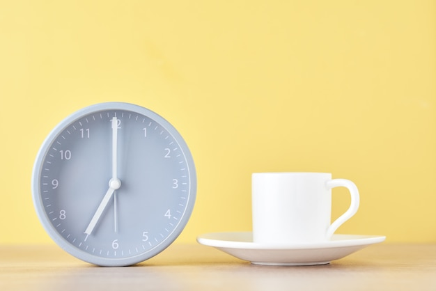Classic gray alarm clock and white coffee cup on a yellow background