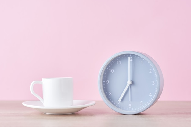 Classic gray alarm clock and white coffee cup