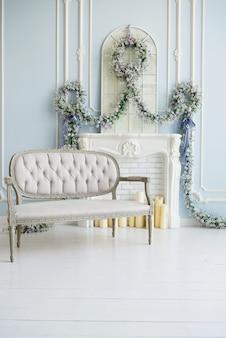 고급스러운 흰색 방에 고전적인 회색 소파. 인공 벽난로. 벽난로에. 방은 꽃으로 장식되어 있습니다.