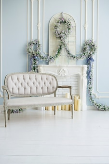 Classic gray sofa in a luxurious white room. artificial fireplace. on the fireplace. the room is decorated with flowers.