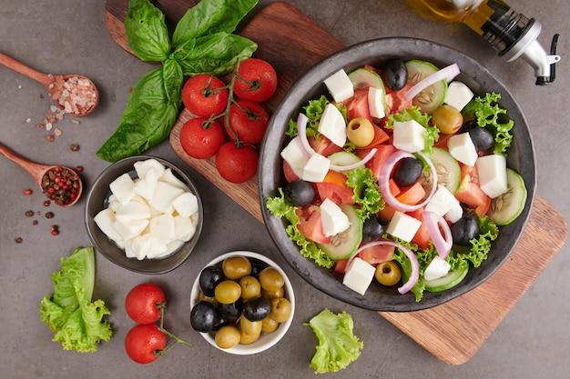 Insalata greca classica di verdure fresche, cetriolo, pomodoro, peperone dolce, lattuga, cipolla rossa, formaggio feta e olive con olio d'oliva. cibo sano, vista dall'alto