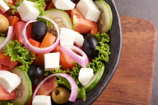 新鮮な野菜、きゅうり、トマト、ピーマン、レタス、赤玉ねぎ、フェタチーズ、オリーブとオリーブオイルのクラシックなギリシャ風サラダ。健康食品、上面図