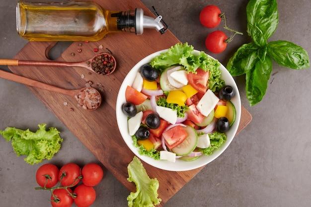 Классический греческий салат из свежих овощей, огурцов, помидоров, сладкого перца, листьев салата, красного лука, сыра фета и оливок с оливковым маслом. здоровая еда, вид сверху