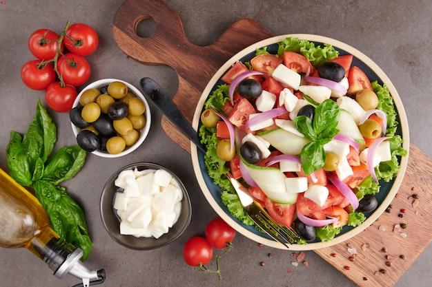 신선한 야채, 오이, 토마토, 달콤한 고추, 양상추, 적 양파, 페타 치즈 및 올리브 오일과 올리브의 고전 그리스 샐러드. 건강에 좋은 음식, 평면도