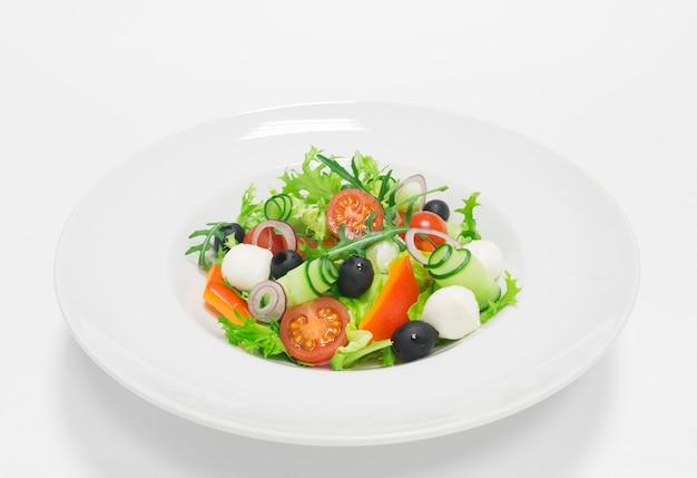 고전적인 그리스 샐러드. 평면도. 흰색 배경. 건강한 먹는 개념. 혼합 매체 프리미엄 사진