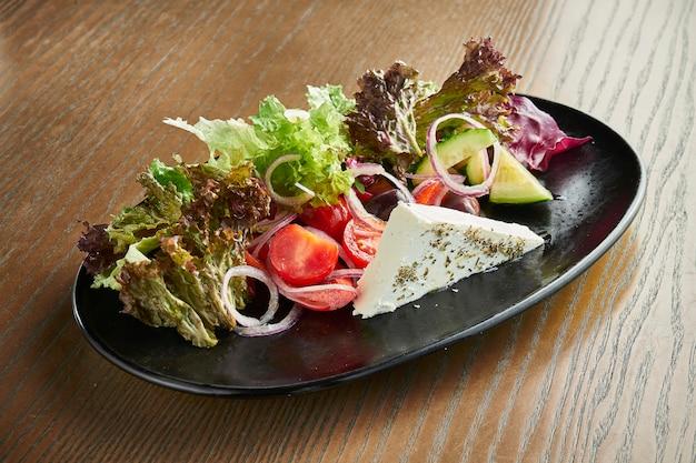古典的なギリシャ風サラダ、トマト、玉ねぎ、キュウリ、フェタチーズ、木製の表面の黒い皿にピタのブラックオリーブ。投稿中のフィルム効果。ソフトフォーカス